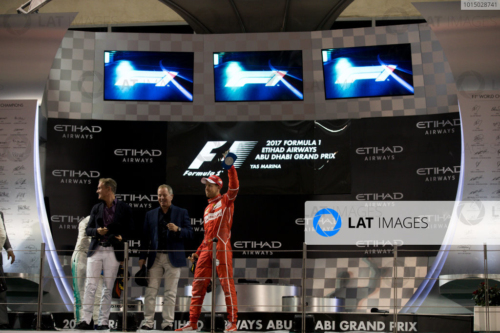 Yas Marina Circuit, Abu Dhabi, United Arab Emirates. Sunday 26 November 2017. Davis Coulthard, Channel 4 F1, Martin Brundle, Sky Sports F1, and Sebastian Vettel, Ferrari, 3rd Position, on the podium. World Copyright: Glenn Dunbar/LAT Images  ref: Digital Image _31I9370