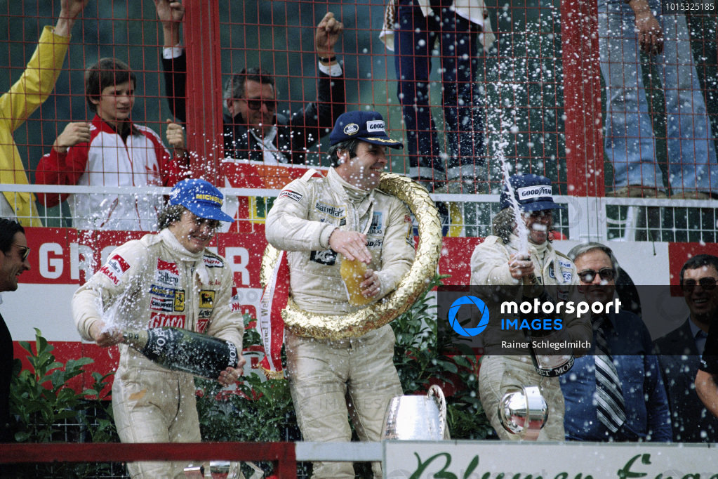 Alan Jones, 1st position, celebrates on the podium with Gilles Villeneuve, 2nd position, and Jacques Laffite, 3rd position.