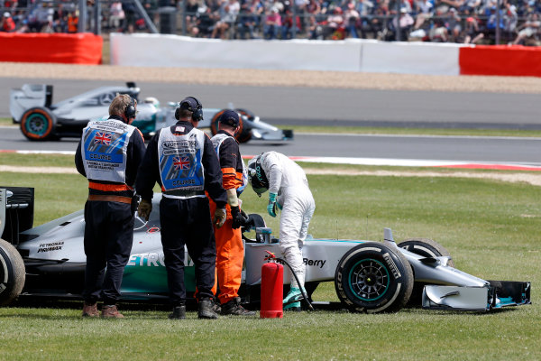Silverstone, Northamptonshire, England. Sunday 6 July 2014. Nico Rosberg, Mercedes F1 W05 Hybrid climbs from his car after retiring from the race as Lewis Hamilton, Mercedes F1 W05 Hybrid passes on track. World Copyright: /LAT Photographic. ref: Digital Image _R6T2603