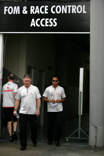 Sepang, Kuala Lumpur, Malaysia 2nd April 2009 Lewis Hamilton, McLaren MP4-24 Mercedes emerges from the Race Control offices with Dave Ryan, Race Team Manager. World Copyright: Andrew Ferraro/LAT Photographic ref: Digital Image VY9E7666