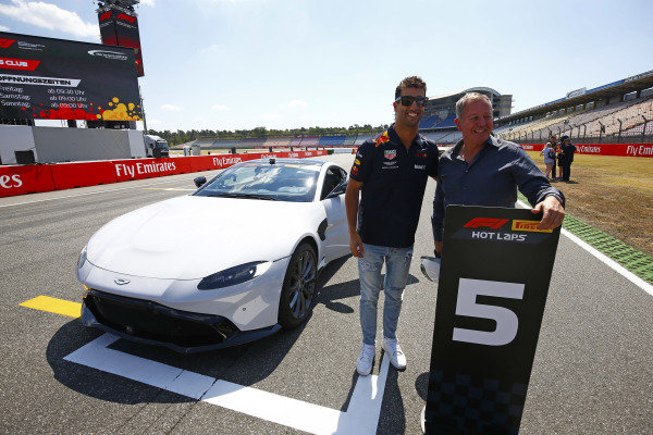 Daniel Ricciardo, Red Bull Racing, and Martin Brundle pose with a Pirelli Hot laps Aston Martin.