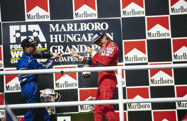 Ayrton Senna, celebrates with newly-crowned World Champion Nigel Mansell, on the podium.