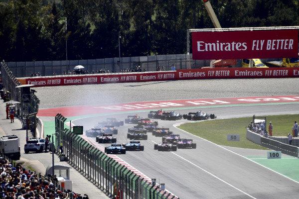 Valtteri Bottas, Mercedes AMG W10, battles with Lewis Hamilton, Mercedes AMG F1 W10, and Sebastian Vettel, Ferrari SF90, ahead of the field as they head through the first corner