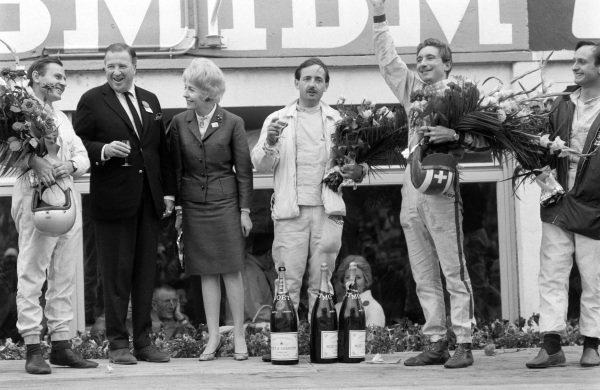 Bruce McLaren and Chris Amon, 1st position, flank Henry Ford II on the podium, as Colin Davis and Jo Siffert, 1st position P2.0 class, enjoy a glass of champagne and wave to the crowd.