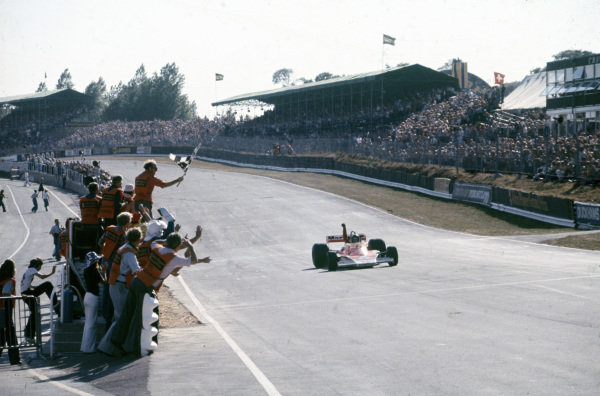 James Hunt, McLaren M23 Ford celebrates as he crosses the finish line in first.