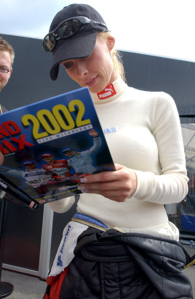 2004 German Mini Championship Lausitzring. Germany. 4th - 6th june 2004. Cora Schumacher checks out an old Grand Prix book for more information on husband Ralf. . World Copyright: Andre Irlmeier/LAT Photographic ref: Digital Image Only