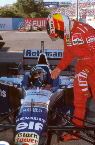 Suzuka, Japan.11-13 October 1996.Damon Hill (Williams Renault) 1st position, is congratulated on being the new World Champion by Michael Schumacher (Ferrari) in parc ferme.Ref-96 JAP 15.World Copyright - LAT Photographic