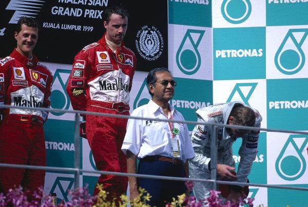 1999 Malaysian Grand Prix.Sepang, Kuala Lumpur, Malaysia. 15-17 October 1999.Eddie Irvine (Ferrari) 1st position, Michael Schumacher (Ferrari) 2nd position and Mika Hakkinen (McLaren Mercedes) 3rd position on the podium.Ref-99 MAL 36.World Copyright - LAT Photographic