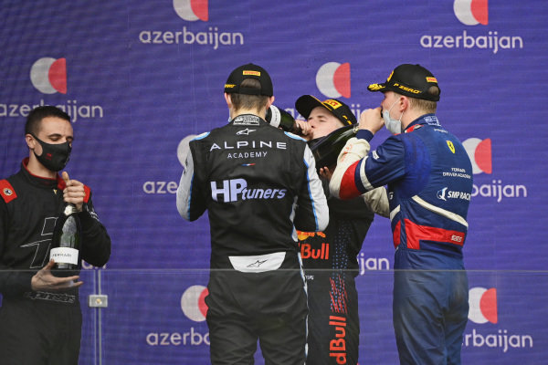 The Hitech Grand Prix representative, Oscar Piastri (AUS, Prema Racing), 2nd position, Juri Vips (EST, Hitech Grand Prix), 1st position, and Robert Shwartzman (RUS, Prema Racing), 3rd position, enjoy champagne on the podium
