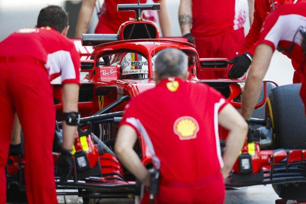 Sebastian Vettel, Ferrari, is serviced by mechanics.