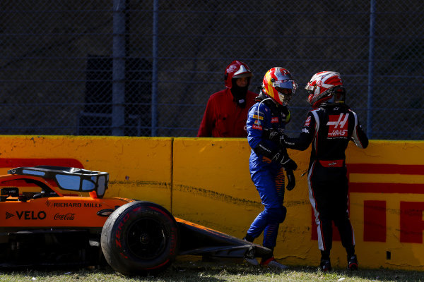 Carlos Sainz, McLaren, and Kevin Magnussen, Haas F1, talk after crashing out of the race