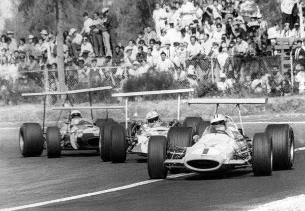 1968 Mexican Grand Prix.Mexico City, Mexico. 3 November 1968.Denny Hulme, McLaren M7A-Ford, retired, leads John Surtees, Honda RA301, retired, and Jack Brabham, Brabham BT26-Repco, 10th position, action.World Copyright: LAT PhotographicRef: Autosport b&w print