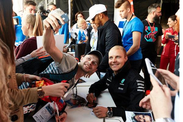 Sochi Autodrom, Sochi, Russia. Thursday 27 April 2017. Valtteri Bottas, Mercedes AMG, has a selfie taken with a fan, while Lewis Hamilton, Mercedes AMG, signs autographs. World Copyright: Steve Etherington/LAT Images ref: Digital Image SNE12005