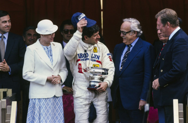 Jody Scheckter celebrates victory on the podium with Prince Rainier III and Princess Grace.