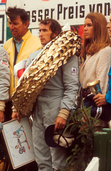 1973 German Grand Prix.Nurburgring, Germany.3-5 August 1973.Jackie Stewart (Tyrrell Ford) 1st position on the podium, with team boss Ken Tyrrell and wife Helen Stewart along side.Ref-73 GER 08.World Copyright - LAT Photographic