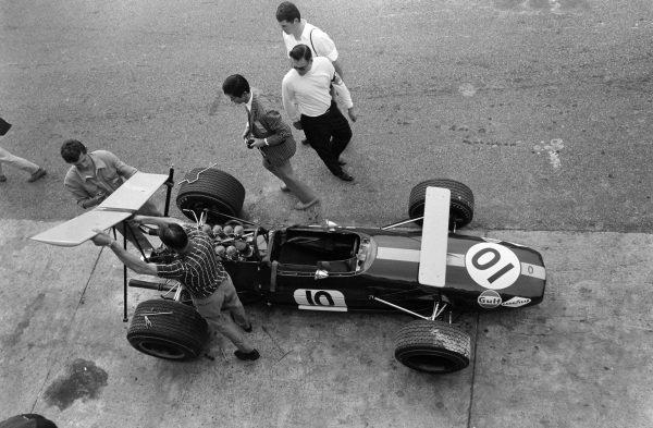 Mechanics affix the rear wing to Jack Brabham's Brabham BT26 Repco.