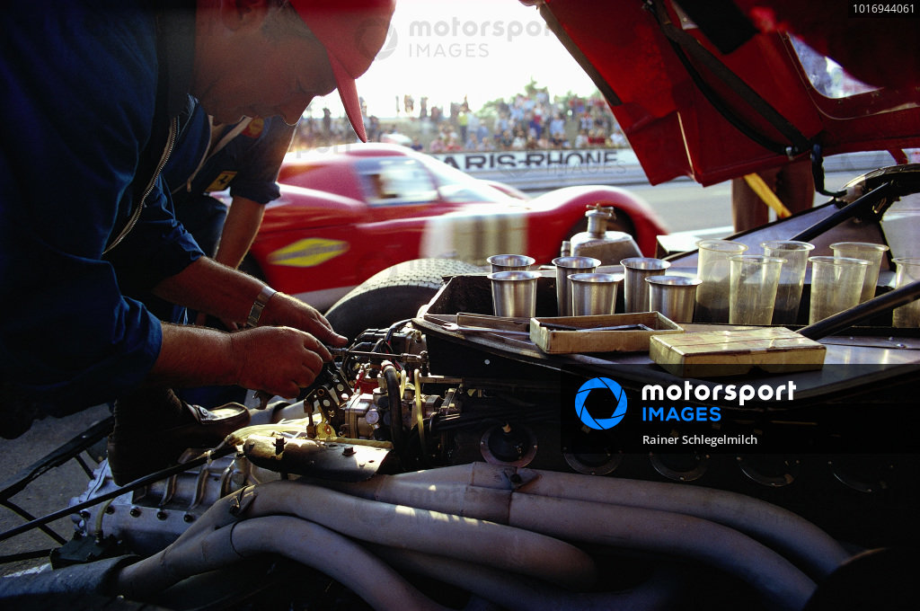 A Ferrari 512 S is worked on whilst the Sam Posey / Ronnie Bucknum, North American Racing Team, Ferrari 512 S leaves the pits.