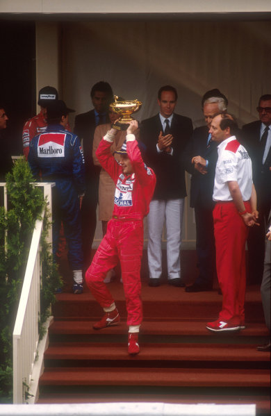 1990 Monaco Grand Prix.Monte Carlo, Monaco.25-27 May 1990.Ayrton Senna (McLaren Honda) celebrates his 1st position on the podium, under the watchful eye of McLaren team boss Ron Dennis. Behind left are Jean Alesi (Tyrrell Ford) 2nd position and Gerhard Berger (McLaren Honda) 3rd position. Also standing with them is HSH Prince Rainier of Monaco and HSH Prince Albert.Ref-90 MON 24.World Copyright - LAT Photographic