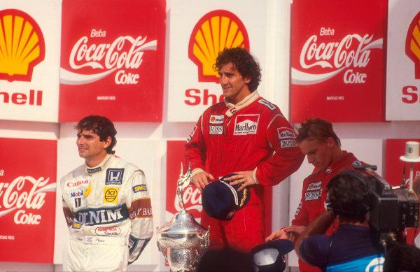 1987 Brazilian Grand Prix.Jacarepagua, Rio de Janeiro, Brazil.10-12 April 1987.  Alain Prost (McLaren TAG Porsche) 1st position, Nelson Piquet (Williams Honda) and Stefan Johansson (McLaren TAG Porsche) 3rd position on the podium.  Ref: 87BRA13. World Copyright - LAT Photographic