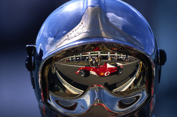 Michael Schumacher, Ferrari F2002, reflected in the visor of a fire marshal.
