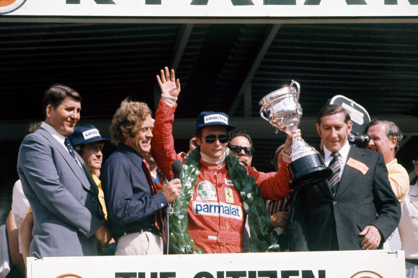 Kyalami, South Africa. 4-6 March 1976. Niki Lauda, Ferrari, receives the winner's trophy on the podium. Ref: 76SA15. World Copyright - LAT Photographic