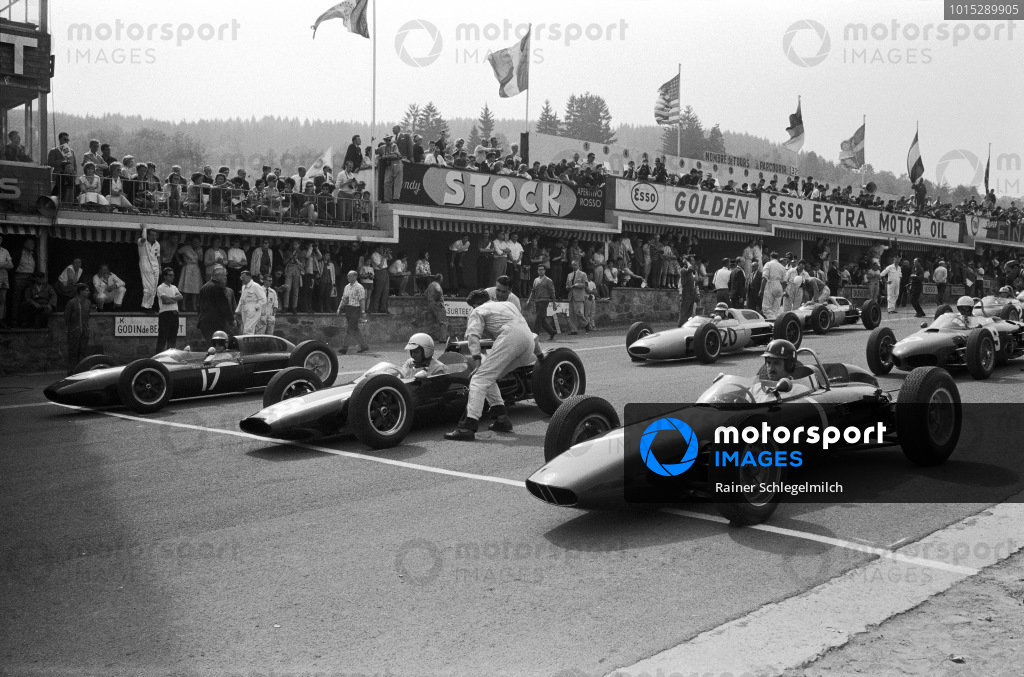 Graham Hill, BRM P57, alongside Bruce McLaren, Cooper T60 Climax and Trevor Taylor, Lotus 24 Climax, on the starting grid.