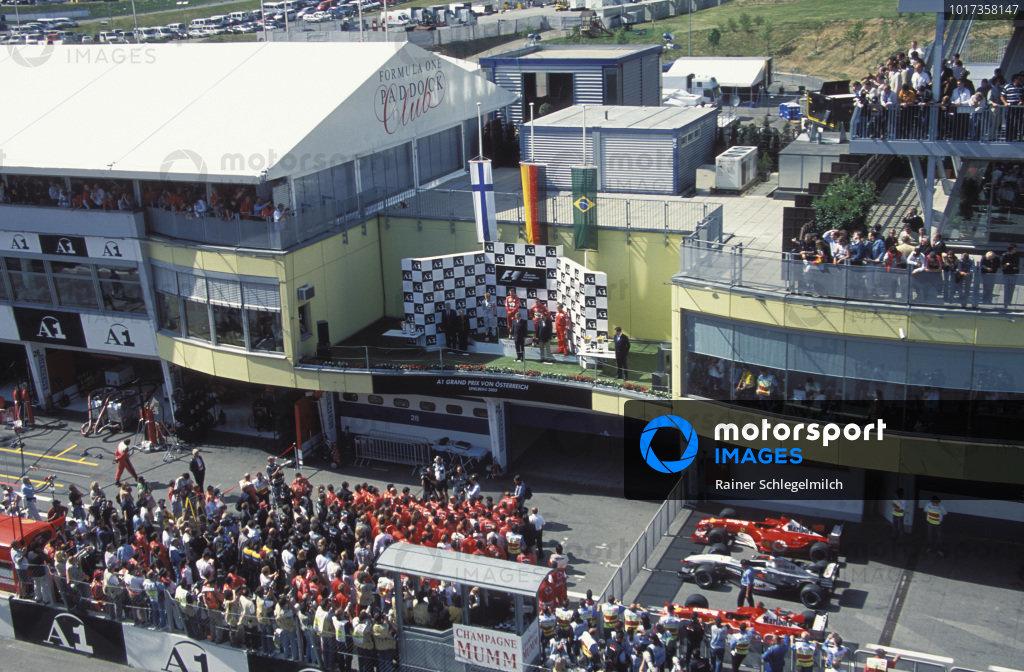 Michael Schumacher, 1st position, Kimi Räikkönen, 2nd position, and Rubens Barrichello, 3rd position, on the podium above the Ferrari and McLaren teams.