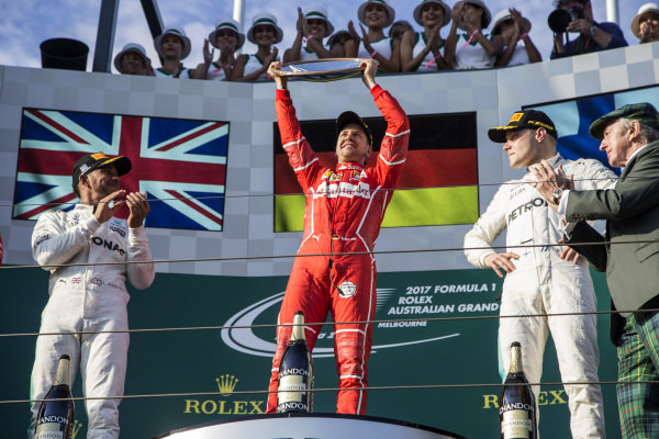Lewis Hamilton (GBR) Mercedes AMG F1, race winner Sebastian Vettel (GER) Ferrari and Valtteri Bottas (FIN) Mercedes AMG F1 celebrate on the podium with the trophy at Formula One World Championship, Rd1, Australian Grand Prix, Race, Albert Park, Melbourne, Australia, Sunday 26 March 2017.
