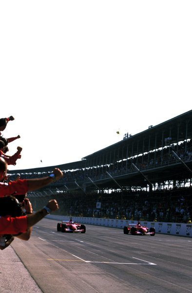 Race leader Michael Schumacher (GER), right, and Rubens Barrichello (BRA), left, slowed down to take a Ferrari formation finish at Indy. Barrichello took the chequered flag from Schumacher by 0.01 of a second causing more controversy for the team. United States Grand Prix, Rd16, Indianapolis, USA. 29 September 2002. BEST IMAGE
