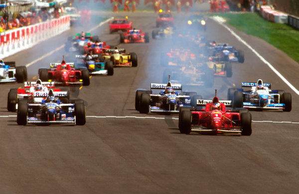 Imola, Italy.3-5 May 1996.Michael Schumacher (Ferrari F310) looks across at rival Damon Hill (Williams FW18 Renault) as they pull away from the grid at the start.Ref-96 SM 04.World Copyright - LAT Photographic