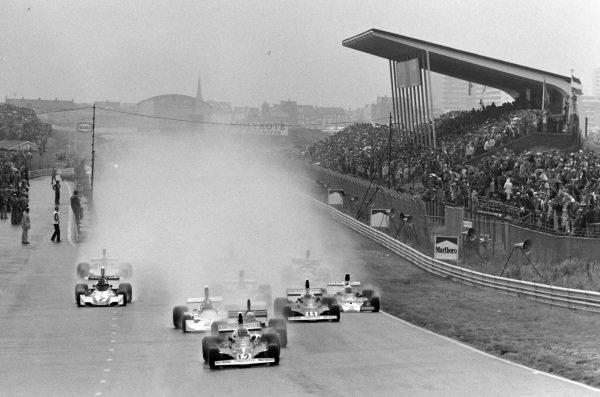 Niki Lauda, Ferrari 312T, leads the pack at the start.