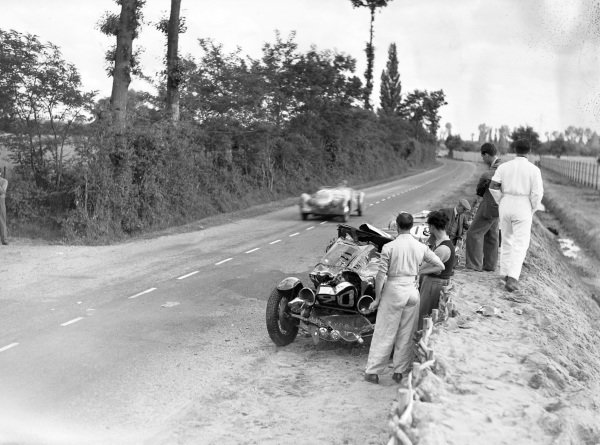 A car passes the abandoned cars of René Kippeurth / René Poulain, Bugatti T44, and Eugène Chaboud / Jean Tremoulet, Delahaye 135CS.