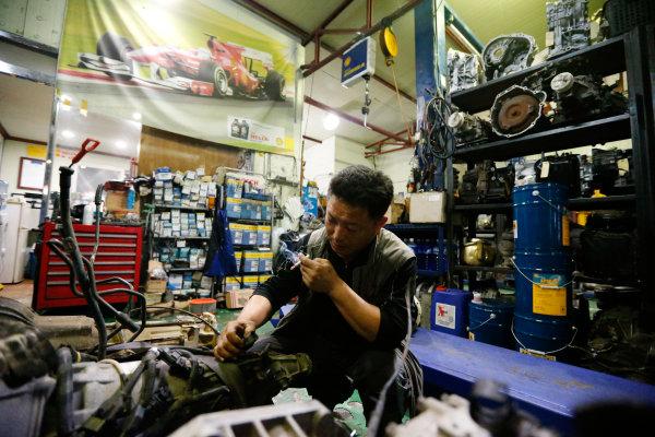 Korea International Circuit, Yeongam-Gun, South Korea. Thursday 3rd October 2013. A mechanic works on his car. World Copyright: Charles Coates/LAT Photographic. ref: Digital Image _N7T8461