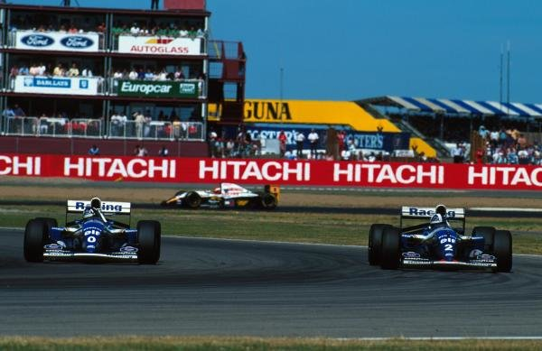Damon Hill (GBR) Williams FW16 passes team mate David Coulthard during qualifying. British Grand Prix, Silverstone, 10 July 1994