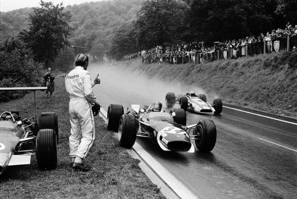 Jo Siffert, Lotus 49 Ford, stops to borrow a dry visor from Graham Hill. John Surtees, Honda RA301, passes.