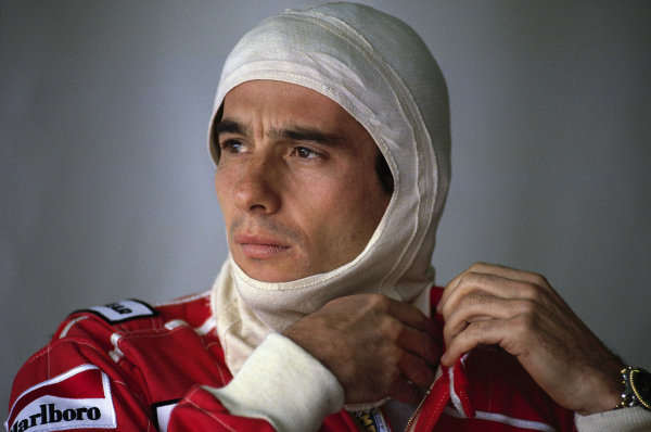 Ayrton Senna puts on his balaclava and does up his fireproof suit in the McLaren garage as he prepares to head onto circuit.