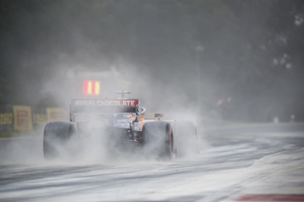 Carlos Sainz Jr., McLaren MCL34, kicks up cement dust which was laid down to cover a heavy oil spill in the F2 race prior to the session