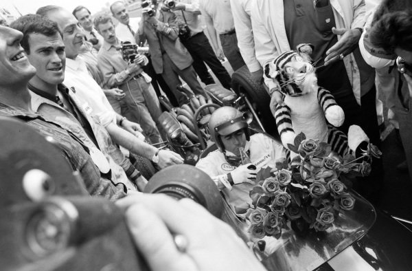 Race winner Jack Brabham returns to the pit lane with victory flowers and Esso mascot.