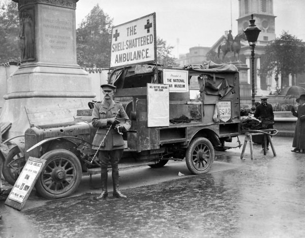 An Austin ambulance damaged by shell fire on display in Trafalgar Square as part of a flower show organised to raise funds for the French Red Cross.