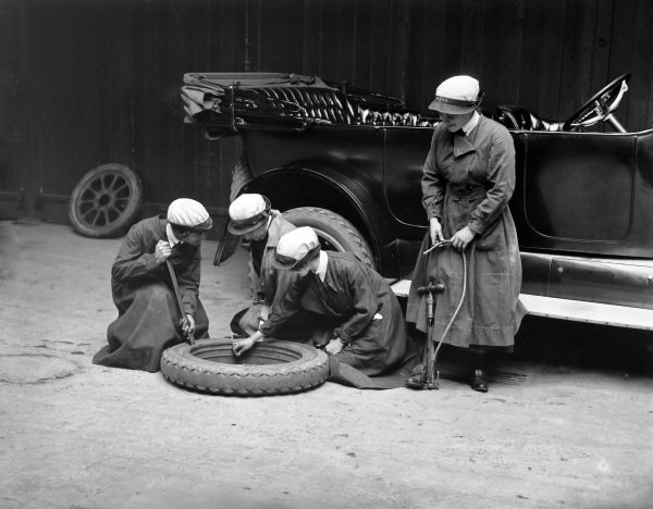 Members of the Women's Royal Naval Service change a tyre on a Cadillac during their driver training at the WRNS Garage in Charing Cross.