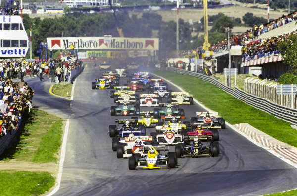 Keke Rosberg, Williams FW09B Honda, leads Nigel Mansell, Lotus 95T Renault, and Alain Prost, McLaren MP4-2 TAG, into the first corner.