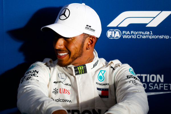 Lewis Hamilton, Mercedes AMG F1, relaxes after setting pole position.