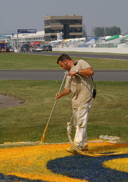 2003 Champ Car Series 22-24 August 2003Molson Indy Montreal Circuit Gilles Villeneuve.Montreal, Quebec, Canada. Track worker painting the infield grass signs in turn 2.2003- Dan R. Boyd USA LAT Photography
