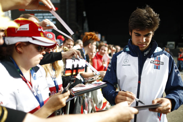 Lance Stroll, Williams Racing, signs autographs for fans.