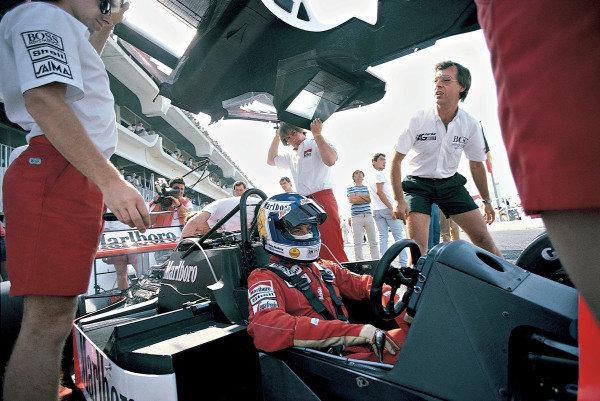 Mechanics lift bodywork over Keke Rosberg, McLaren MP4-2C TAG, in the pits.