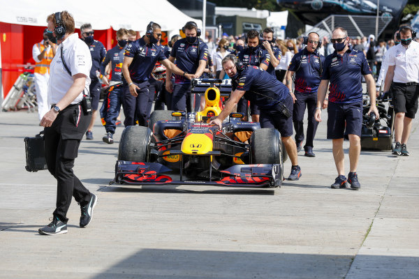 A Red Bull is wheeled through the paddock
