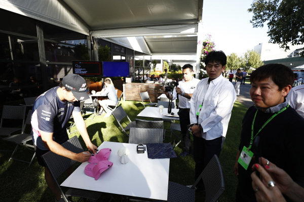 Sergio Perez, Racing Point signs hats for guests in the paddock