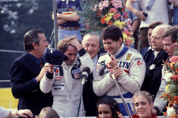 Jody Scheckter celebrates victory on the podium with Jacques Laffite, 2nd position, and Didier Pironi, 3rd position.