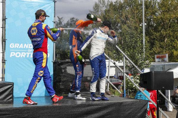 #10: Alex Palou, Chip Ganassi Racing Honda, #27: Alexander Rossi, Andretti Autosport Honda, #9: Scott Dixon, Chip Ganassi Racing Honda celebrate on the podium with champagne