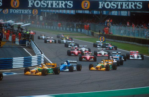 1993 British Grand Prix.Silverstone, England.9-11 July 1993.Michael Schumacher (Benetton B193B Ford) followed by Martin Brundle (Ligier JS39 Renault), Riccardo Patrese (Benetton B193B Ford), Johnny Herbert (Lotus 107B Ford), Jean Alesi (Ferrari F93A), Mark Blundell (Ligier JS39 Renault) and Michael Andretti (McLaren MP4/8 Ford) through Copse at the start. Ref-93 GB 12.World Copyright - LAT Photographic
